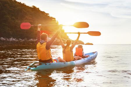 Foto de Happy family is walking at sunset sea by kayak or canoe. Active tourism concept - Imagen libre de derechos