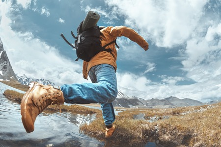 Photo pour Hiker jumps across water in mountains area. Hiking concept with man - image libre de droit