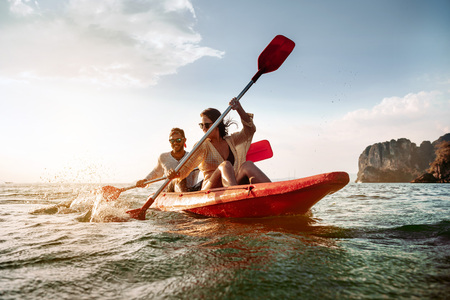 Foto de Happy couple walks by sea kayak or canoe at tropical bay - Imagen libre de derechos