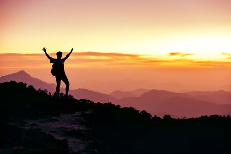 Photo for Hikers or travelers silhouette stands on mountain top against sunset with raised arms - Royalty Free Image