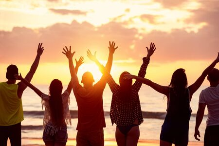 Photo pour Silhouettes of six happy friends with raised arms stands against beautiful sunset sea beach - image libre de droit