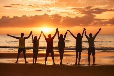 Photo for Group of happy friends are having fun with raised arms together at sea beach and enjoy sunset - Royalty Free Image