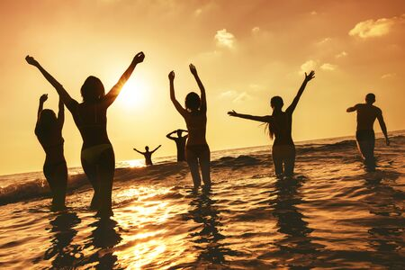 Photo pour Big group of happy peoples stands at sunset sea beach. Silhouettes with raised arms - image libre de droit
