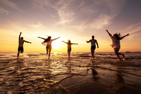 Photo for Five happy friends runs with raised arms at sunset beach - Royalty Free Image