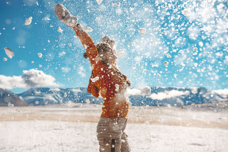 Photo pour Adult girl throws snow and having fun against mountains. First snow concept - image libre de droit