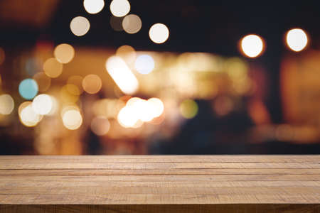 Photo pour Empty dark wooden table in front of abstract blurred bokeh background of restaurant, pub or bar. Blurred background for product display or montage your products with several concept idea and any occasion. - image libre de droit