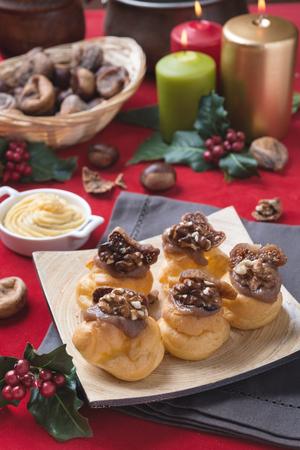 Bigne alla crema di castagne con fichi e noci su sfondo natalizio