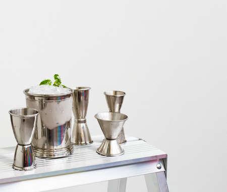Foto de Mint julep whiskey cocktail in misted frozen metal glass and bar accessories set of jiggers on white background. Restaurant menu, alcohol recipe decor, specialized website blog design. - Imagen libre de derechos
