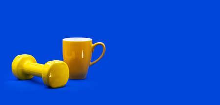 Foto de Home workout self isolation gym online sport concept. A yellow dumbbell, tea cup on contrast vibrant blue background with free copy space for text. Website banner, social media profile header, card - Imagen libre de derechos