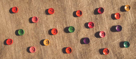 Foto de Variety of Bright colorful orange yellow red blue green wooden buttons on brown rustic linen fabric. A horizontal pattern background for website leaderboard, social network group header or banner - Imagen libre de derechos