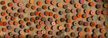 Foto de Variety of bright ethnic boho style orange yellow red wooden buttons on brown rustic linen fabric. A horizontal pattern background for website leaderboard, social network group header or banner - Imagen libre de derechos
