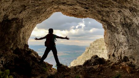 Photo pour the magnificent caves at the peaks of the mountains and the happiness of the man overlooking the city - image libre de droit
