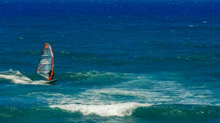 PAIA, UNITED STATES OF AMERICA - AUGUST 10 2015: a wind surfer on an upwind reach at hookipa