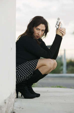Hispanic woman behind a wall holding a handgun in ready to fire position.