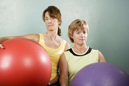 Two Physically Fit Women Posing With Exercise Balls