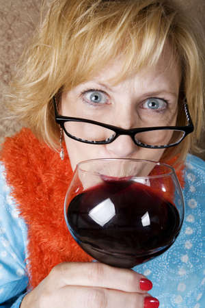 Crazy woman with wild eyes drinking wine