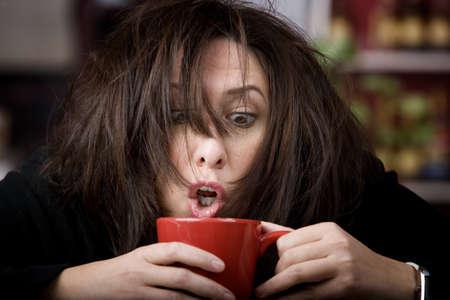 Half awake woman cradling a mug of coffee