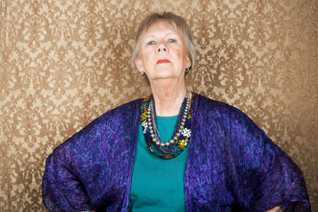 Portrait of snooty senior woman in front of gold background
