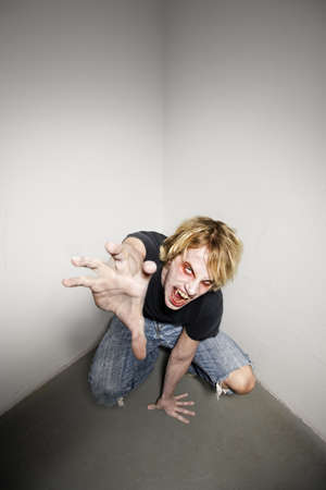 Young blonde male zombie reaching towards the camera