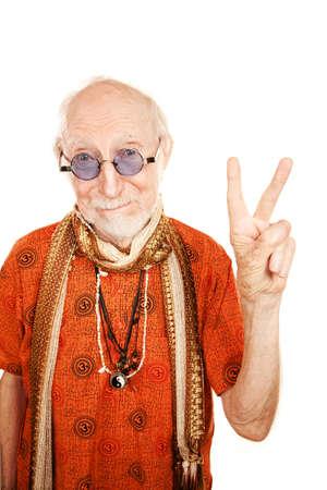New age senior man in orange shirt making peace sign