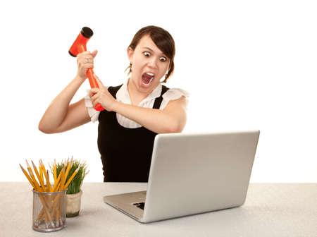 Pretty female office worker destroying laptop computer