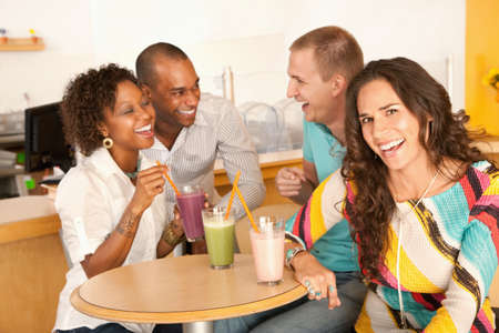 A group of young friends are socializing over smoothies.  One woman is smiling at the camera.  Horizontal shot.