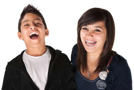 Two hispanic kids laughing on white background