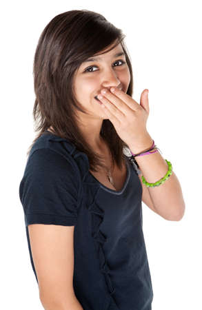 Cute Hispanic teenage girl covering her braces with hands and a big smile