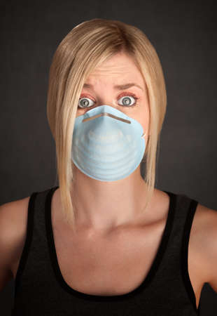 Worried young blonde woman with surgical mask on a grey background