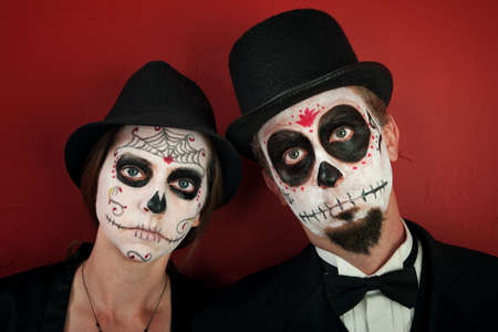Serious couple in skull and cobweb makeup with hats