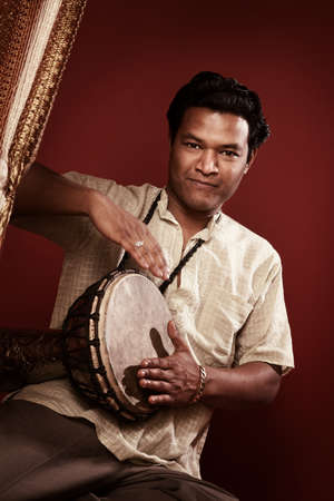 Handsome Indian man on maroon background plays a drum