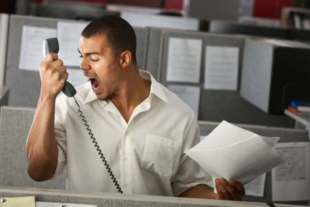 Angry Latino office worker yells on phone