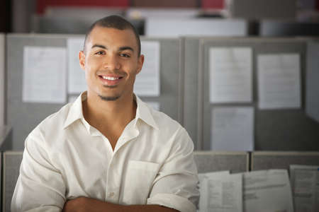 Confident office worker smiles in his office cubicle
