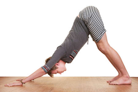 Young Caucasian man in Adho Mukha Svanasana Yoga posture over white background