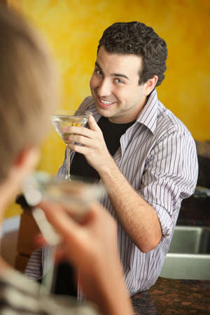 Happy young Caucasian man enjoys martini with his friend in kitchen