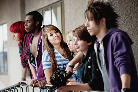 Attractive young teen punk looks at the camera while the rest of her friends ignore it.