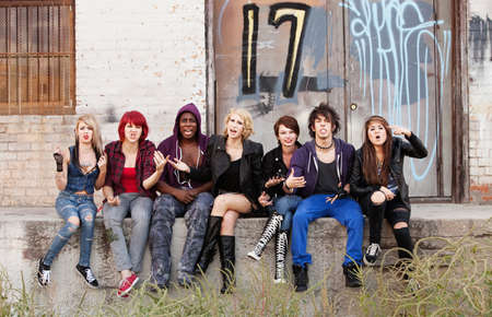 A group of young teen punks shout angrily as their photo is taken.