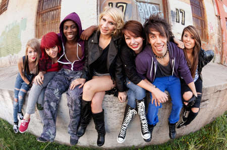 Attractive group of teen punks smile for the camera as they sit behind an abandoned warehouse.