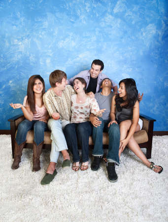 Group of six laughing friends on couch
