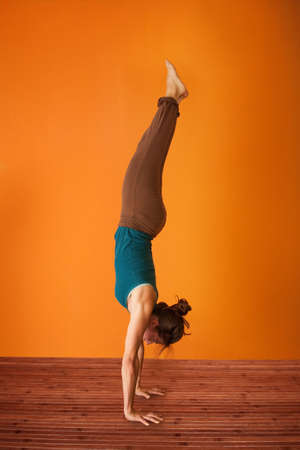 Woman in the Adho Mukha Vriksasana Yoga position
