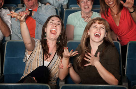 Foto de Young women laugh out loud in theater  - Imagen libre de derechos