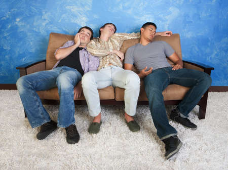 Three tired young men sleep on a sofa