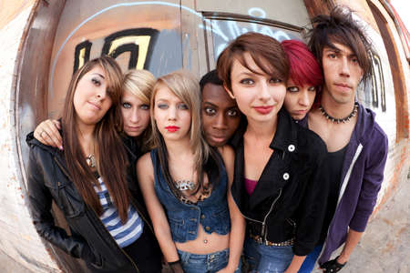 Young teen punks pose for a serious group photo behind an abandoned building.
