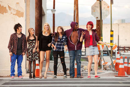 Young and happy gang of teen punks cross the street together.