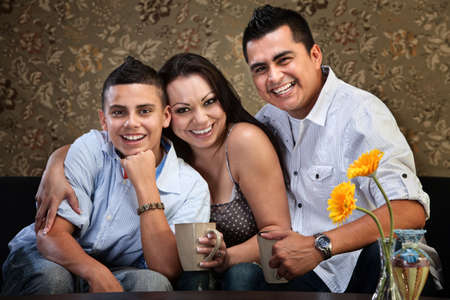 Happy Latino family of three embracing on a sofa