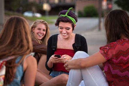 Teenager and friends playing with a cell phone