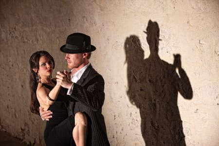 Attractive tango dancers under spotlight in urban setting