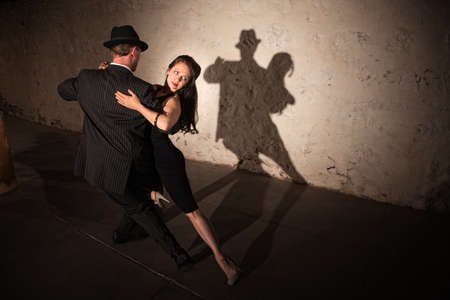 Beautiful woman with dance partner performing a tango routine