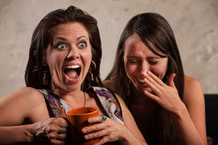 Screaming woman holding coffee mug next to laughing friend
