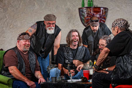 Six male biker gang members laughing with weapons on table